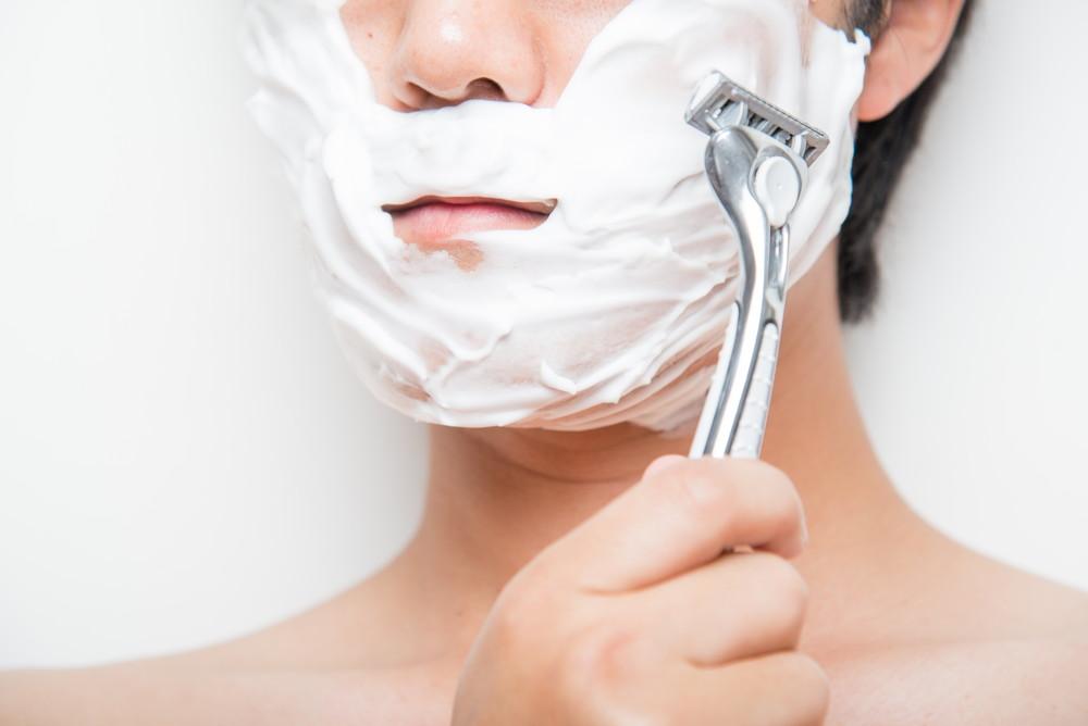 剃刀で顔を剃る男性