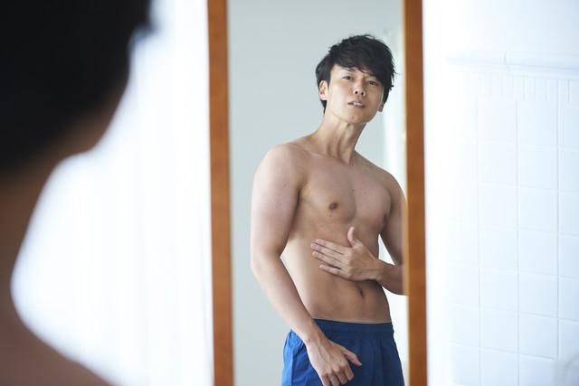 鏡で体をチェックする男性