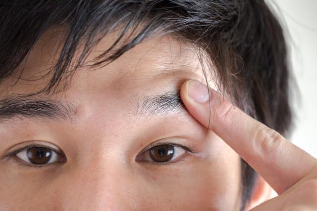 眉毛を触る男性